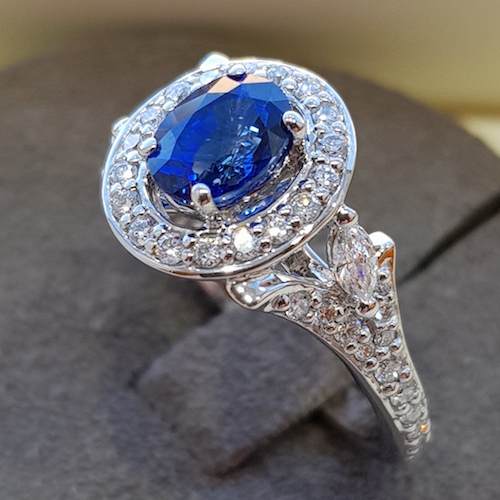 Oval blue halo sapphire and diamond platinum ring, floral design on ring